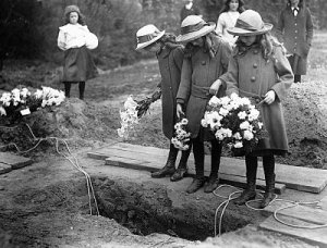 Girls Standing over Grave at Funeral